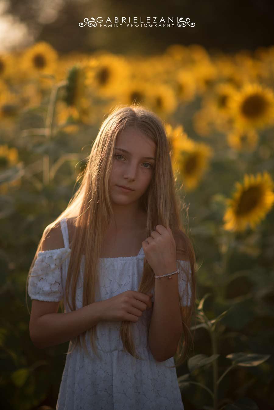 fotografo bambini con fiori bimba tra i girasoli bionda