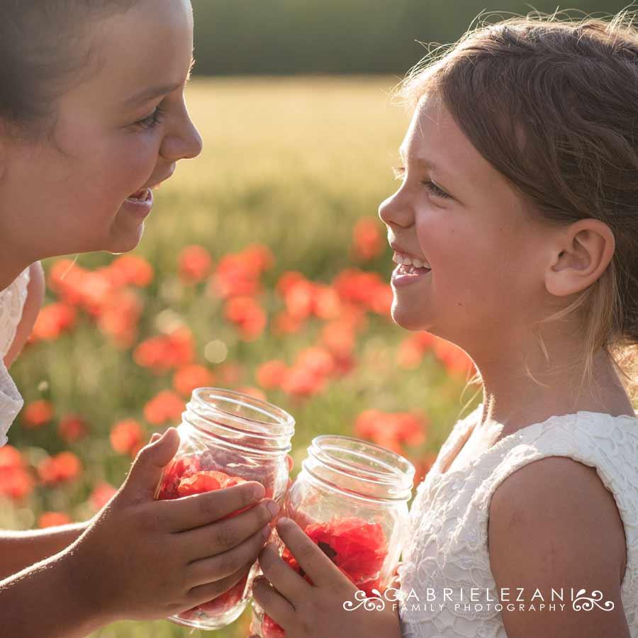 fotografo bambini con fiori bimbe campo papaveri sorelle