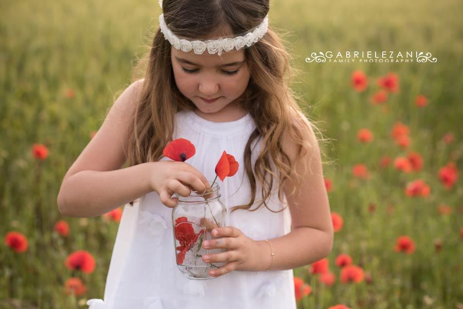 fotografo bambini con fiori esterno campo papaveri