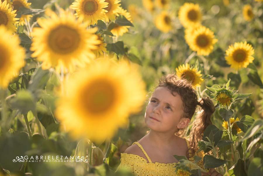 fotografo bambini con fiori bimba esterno girasoli estate