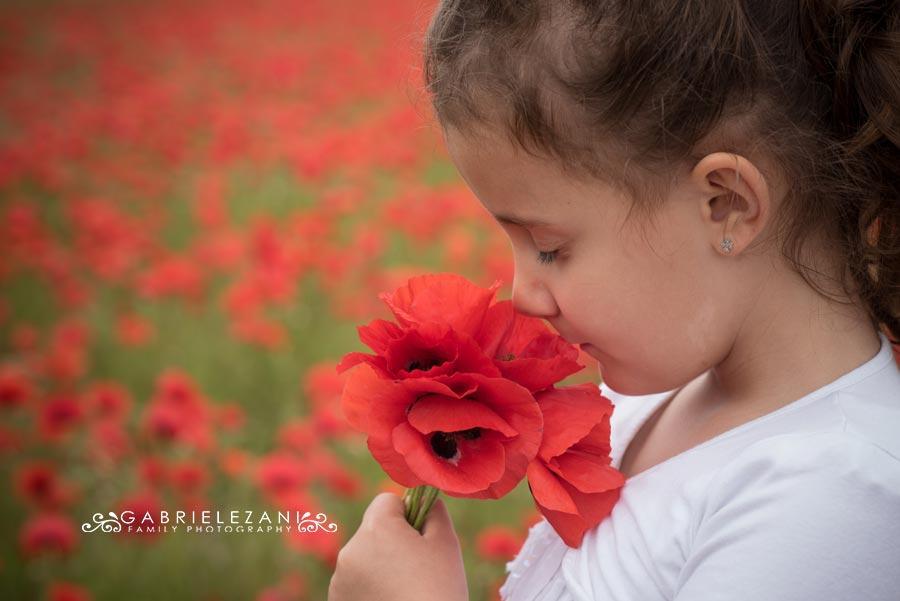 fotografo bambini con fiori papaveri profumo rosso