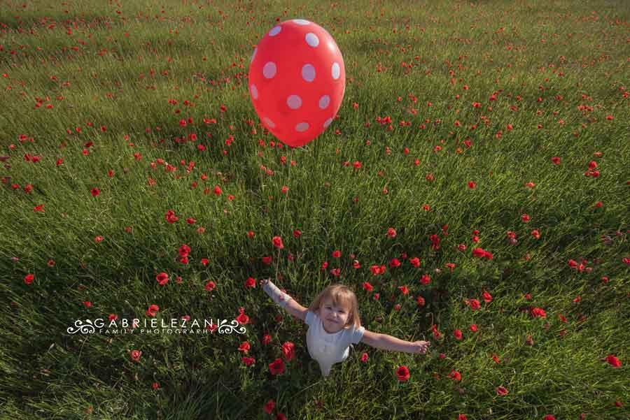 foto bambini campo di papaveri dall'alto pallocino rosso