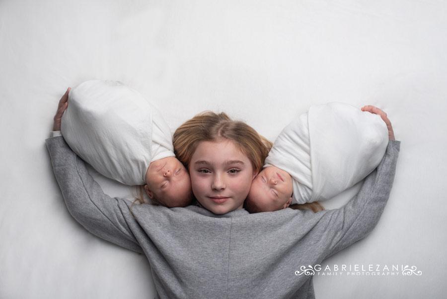 fotografo neonati gemelli la spezia gabriele zani due neonati in braccio a bambina bionda