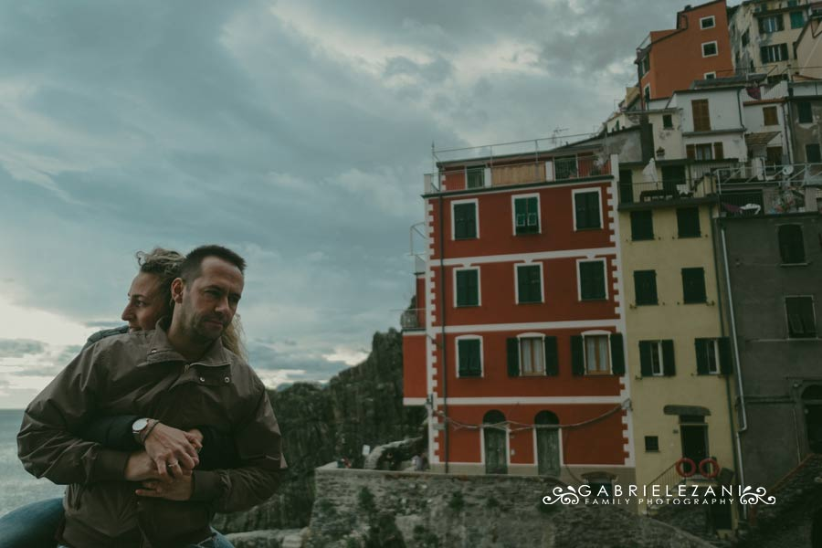 fotografo engagement cinque terre abbraccio con Riomaggiore sullo sfondo
