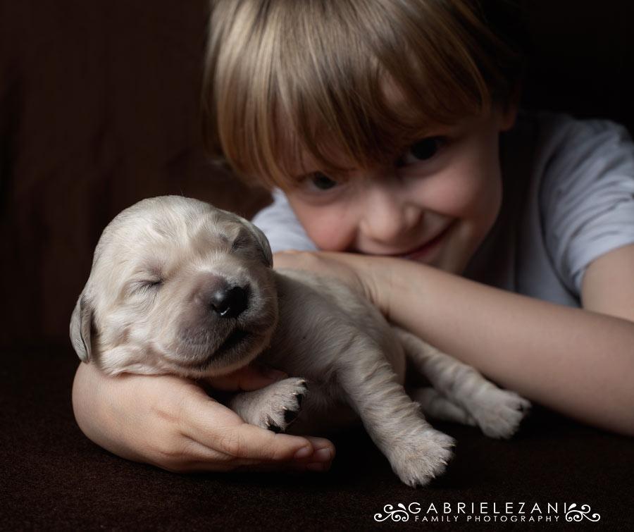 fotografo famiglie e animali bimbo sdraiato con cucciolo di cane
