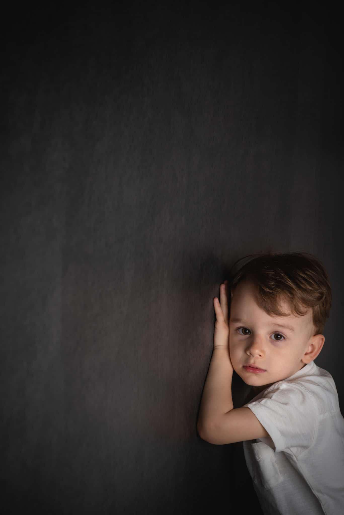 fotografo ritratti in grigio la spezia scegli il tuo colore bambino appoggiato al muro