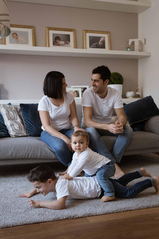 fotografo famiglia in casa la spezia genitori sul divano con bimbi che giocano sul tappeto